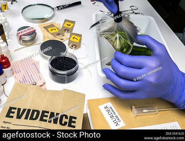 Expert Police get fingerprints from a broken glass bottle in Criminalistic Lab, conceptual image