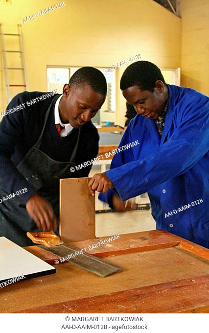 School boy clamping wood with teacher in woodwork classroom, St Mark's School, Mbabane, Hhohho, Kingdom of Swaziland