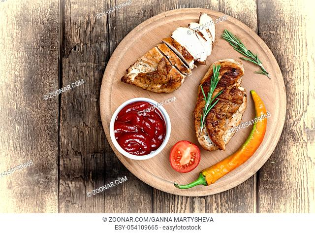 Authentic steak barbecue with rosemary on a wooden board. Chicken steak barbecue