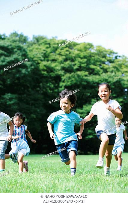Japanese kids running in a city park