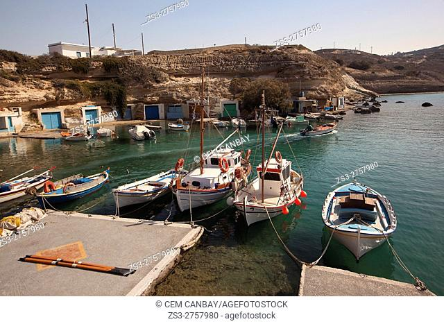 View to the fisherman houses with boat shelters in Mandrakia village with a fisherman leaving the shelter in his boat at the background, Milos, Cyclades Islands