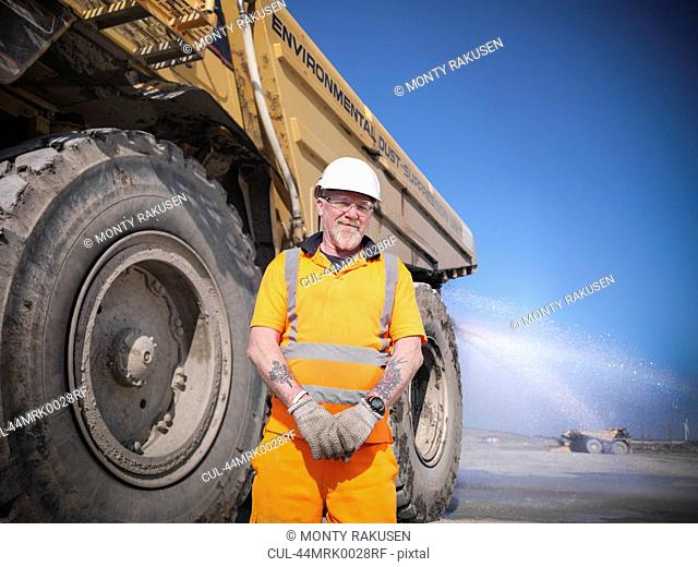 Worker standing by truck at coal mine