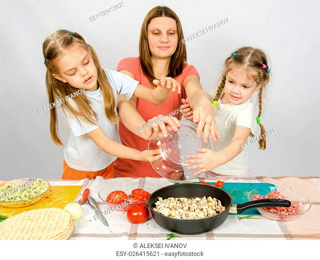 Mother with two daughters at the kitchen table with a plate of mushrooms is poured into the pan