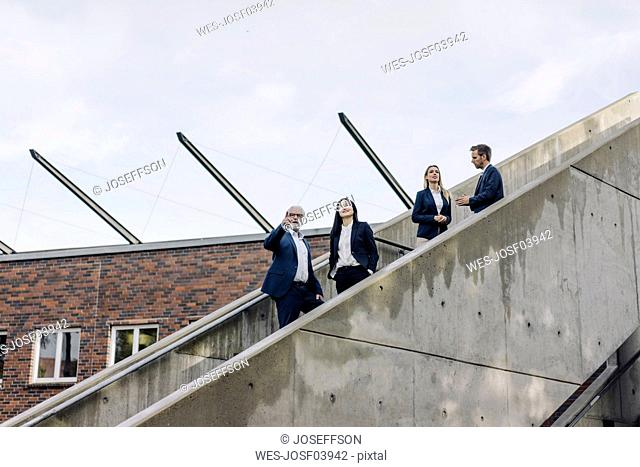 Business people standing on exterior stair