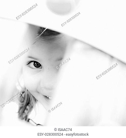Little girl playing hide and seek in a playground