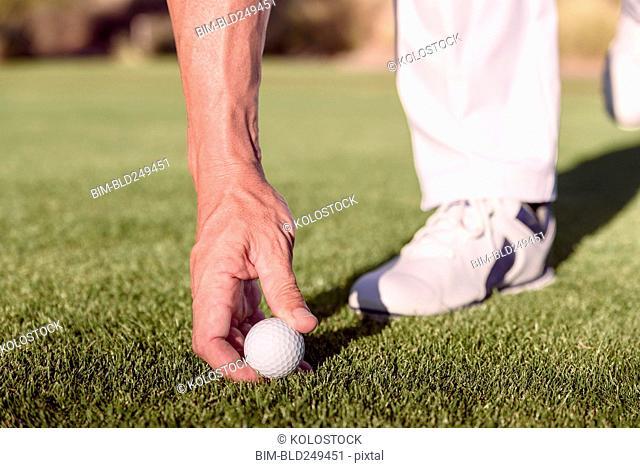 Hispanic golfer placing golf ball on tee