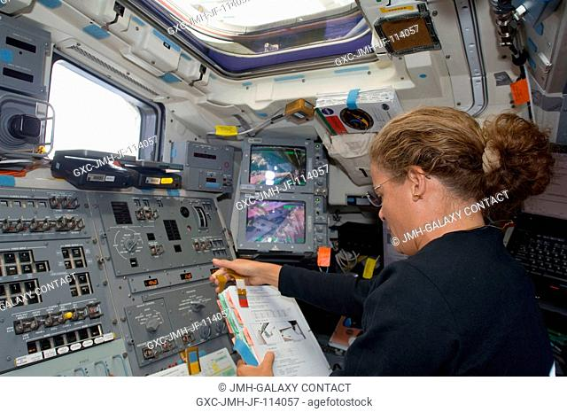Canadian Space Agency astronaut Julie Payette, STS-127 mission specialist, looks over a checklist on the aft flight deck of Space Shuttle Endeavour while docked...