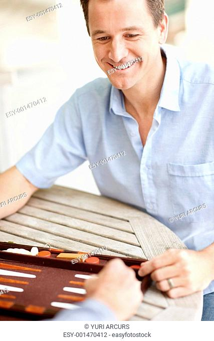 Portrait of happy young man enjoying a game of backgammon