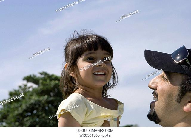 Father picking up daughter at park ,smiling
