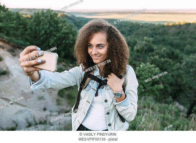 Smiling teenage girl taking selfie in nature