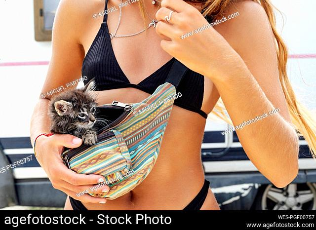 Young woman with kitten in waist pack