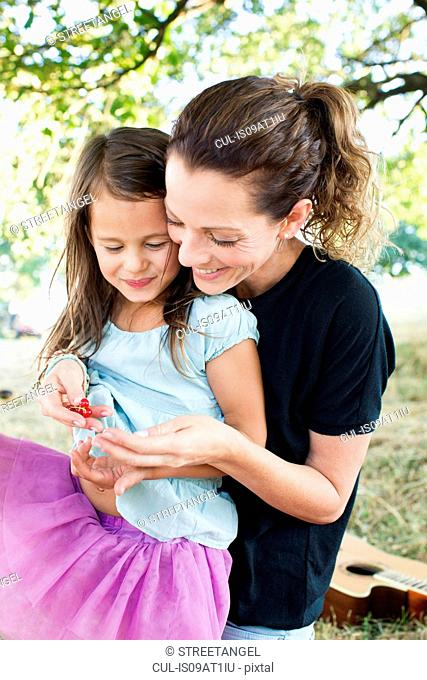 Mature woman and daughter sitting in park eating redcurrants