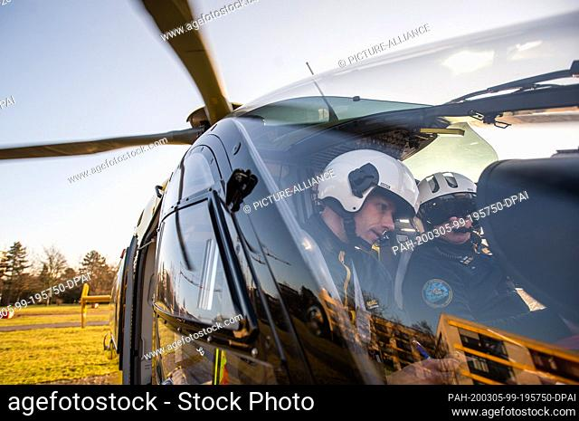 02 March 2020, Lower Saxony, Wolfenbüttel: Pilot Christian Schälicke (l) and emergency paramedic Martin Losse are sitting in the cockpit of ADAC Luftrettung's...