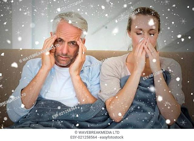 Composite image of sick couple sitting on the couch under a blanket