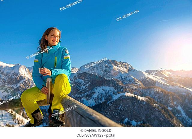 Mid adult woman sitting on fence on mountain holding flask looking away smiling, Jenner, Berchtesgadener, Germany