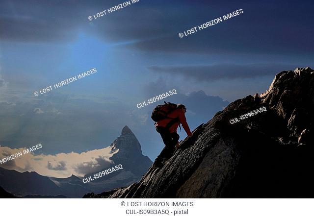Senior male climber climbing rock face near Matterhorn, Canton Wallis, Switzerland
