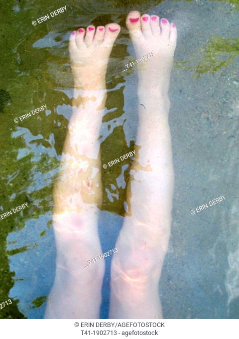 A young girl's legs underwater
