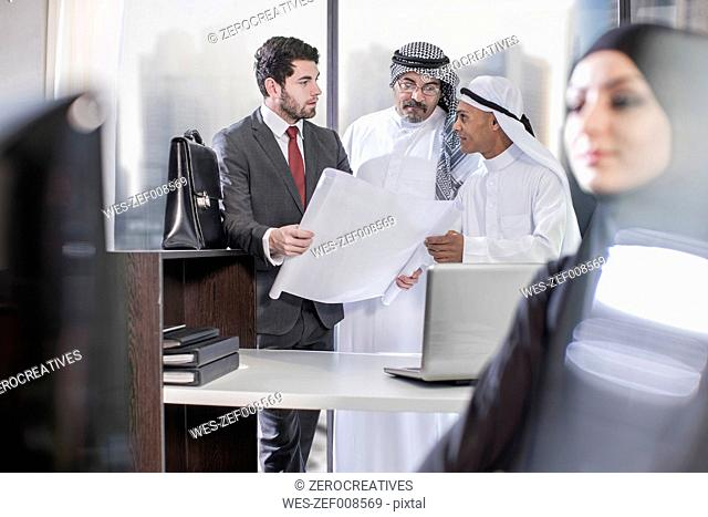 Businessman discussing plans with Middle Eastern collegues