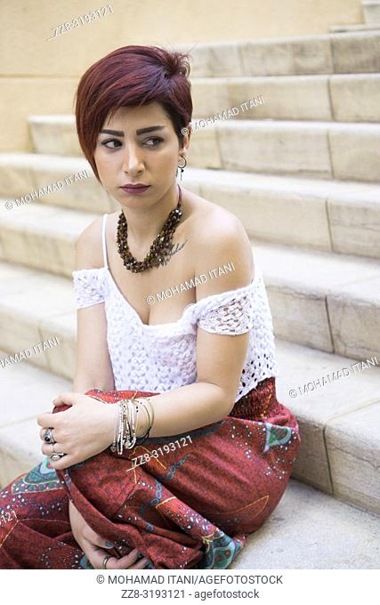 Stylish young woman with short red hair sat on the steps outdoors looking away