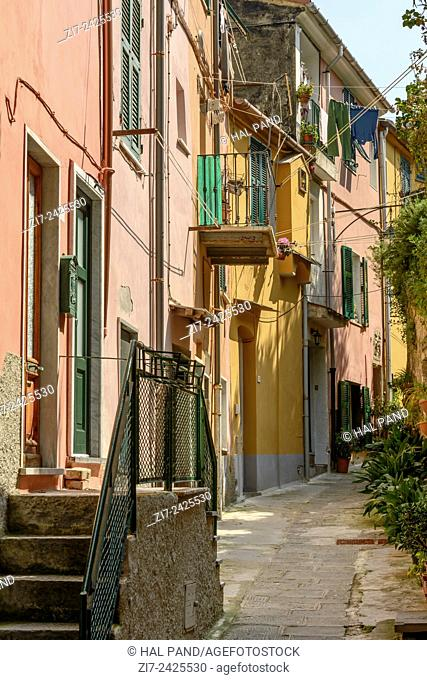 view of old houses on narrow uphill lane in medieval village, shot on a sunny spring day, Portovenere, italy