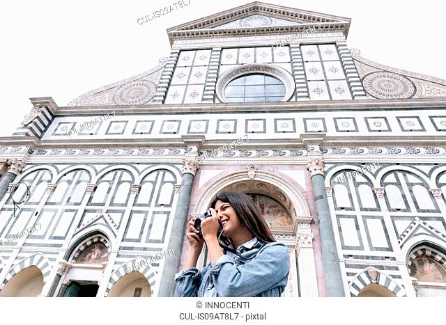 Low angle view of young woman using digital camera in front of church, Piazza Santa Maria Novella, Florence, Tuscany, Italy