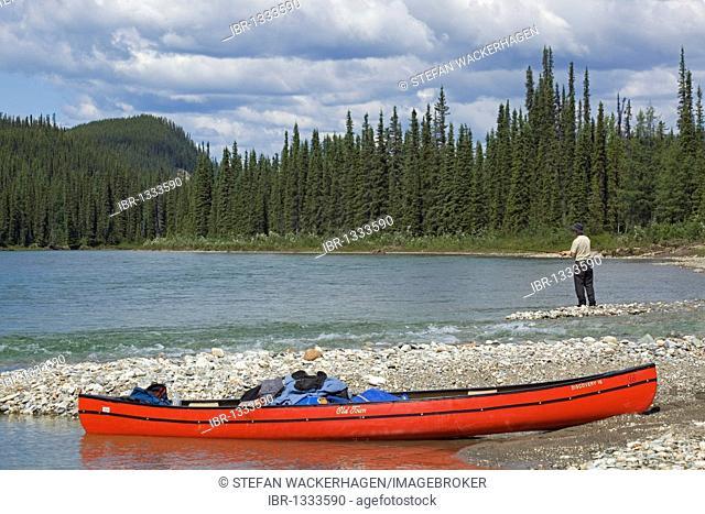 Loaded canoe on shore of upper Liard River, man fishing behind, gravel bar, Yukon Territory, Canada