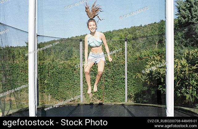 Horizontal photo of a smiling young brunette teenager jumping on a trampoline with net around on the green yard outdoors