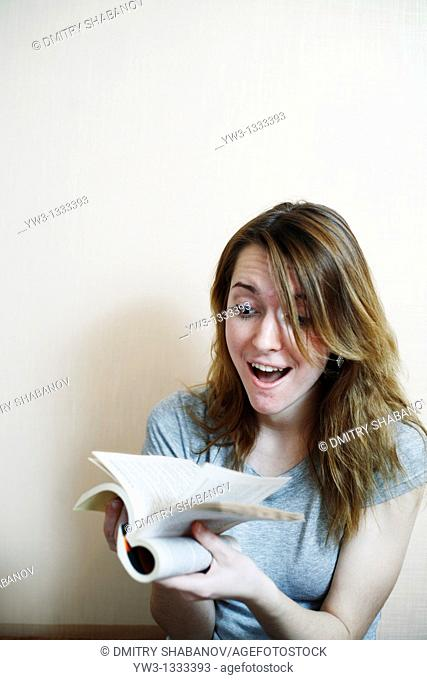 pretty girl against light wall with book
