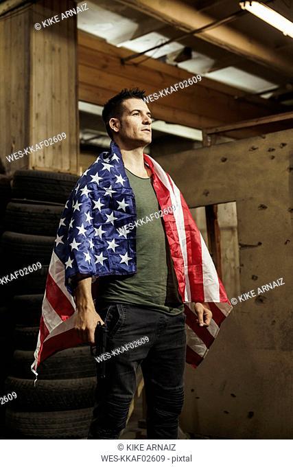 Man wearing American flag holding a gun