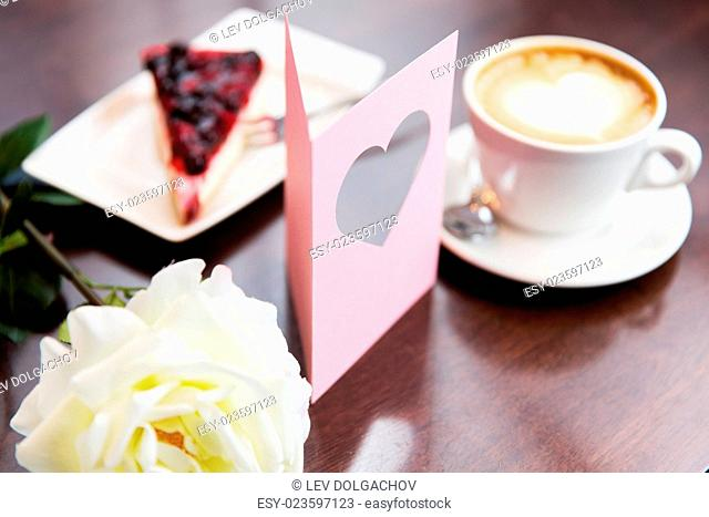holidays, valentines day and love concept - close up of greeting card with heart, flower, cake and coffee