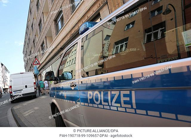 18 July 2019, North Rhine-Westphalia, Cologne: A police car stands in front of a residential building in the city centre