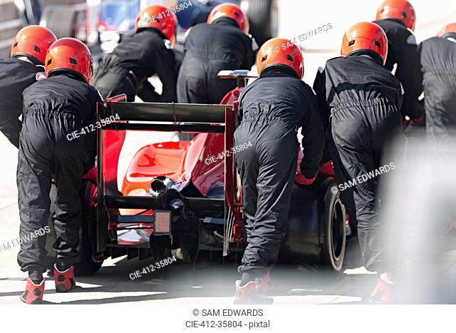 Pit crew pushing formula one race car out of pit lane