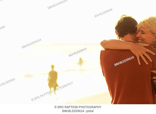 Caucasian couple hugging on beach