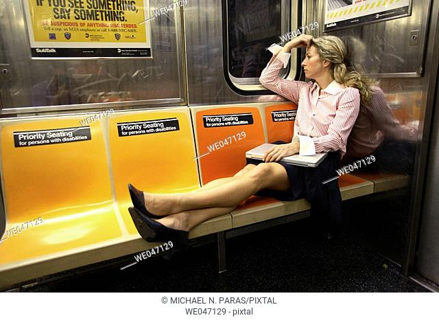Business woman with laptop with legs across subway seats