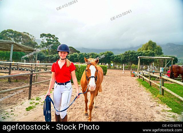 Portrait confident teenage girl leading horse along rural paddocks