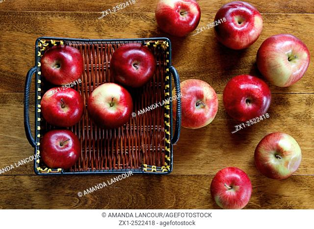Birds eye view of several Apples scattered, inside and outside a basket on wood background