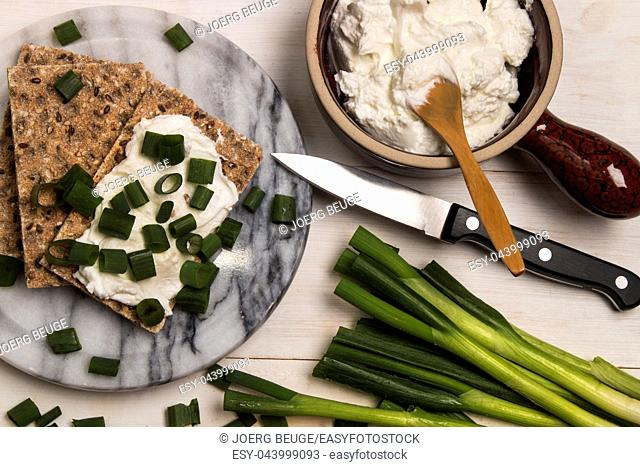 healthy, vegetarian breakfast with crispbread, quark and fresh spring onion on marble