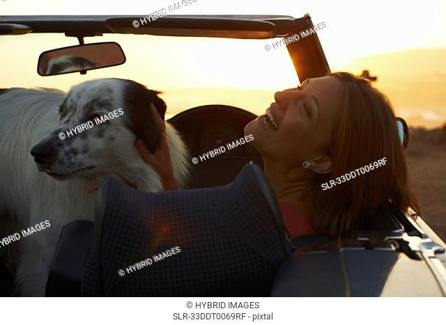 Woman laughing with dog in convertible
