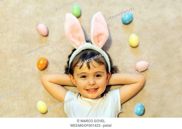 Portrait of happy little girl lying on the floor between Easter eggs