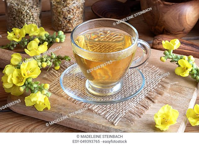 A cup of herbal tea with fresh blooming mullein