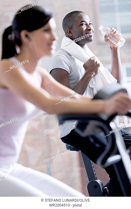 Resting while biking at health club, focus on backgrouhnd