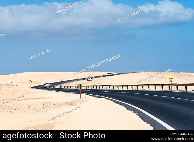 Scenic view of road through sand dunes against sky. Corralejo, Fuerteventura, Canary Islands