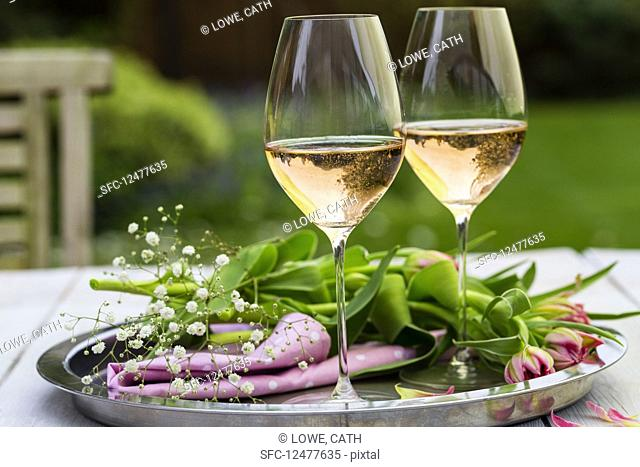Glasses of Rose Sparkling wine in outside garden setting