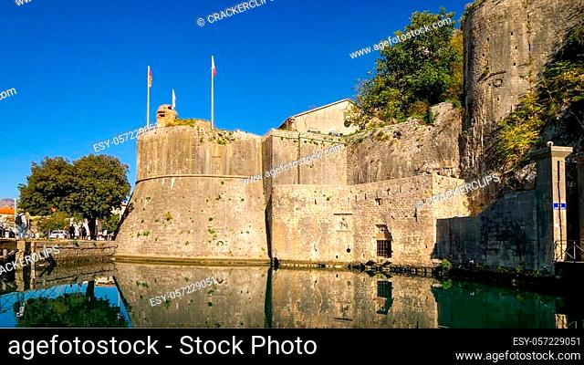 Stone guard tower of Kotor Fortress sits above a moat in Kotor, Montenegro