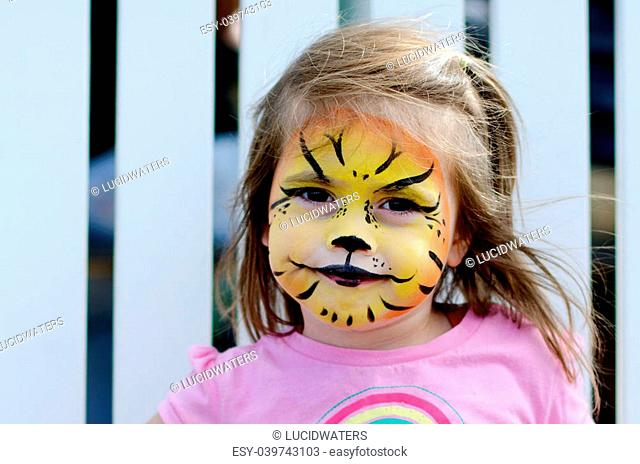 Cute little girl with face painted like a lion