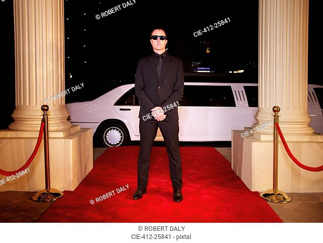 Serious bodyguard in sunglasses protecting red carpet at event