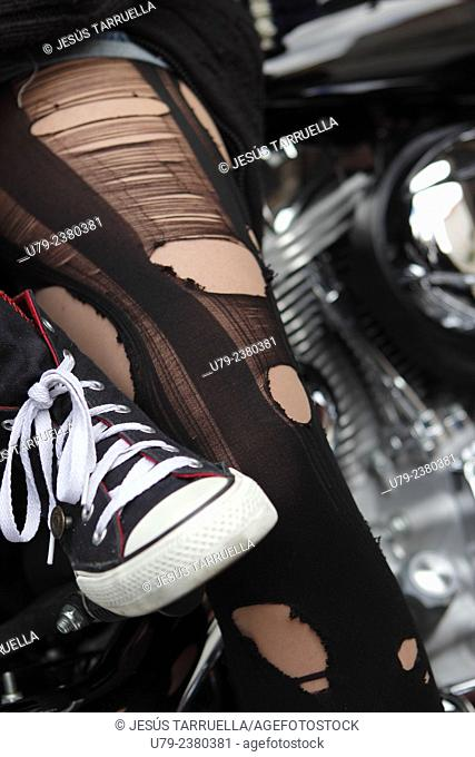 Close-up of a woman biking boots as she sits on the motorcycle with a mans boots in the background