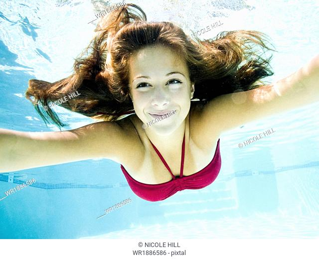 teenage girl in a bathing suit swimming in a pool