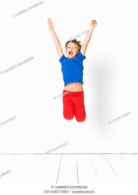 cool, young and cute boy with blue shirt and red trousers is jumping high in the studio in front of white background and white wooden floor