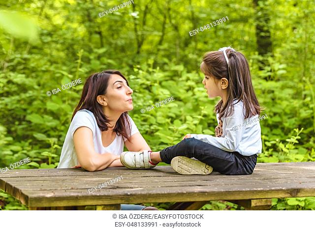 Young mom and her little girl have fun together on wooden bench in forest. Happy mother and daughter moments with love and natural emotion